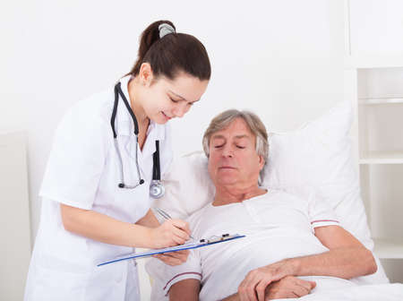 Senior Male Patient Looking At Doctor Writing On Clipboard photo