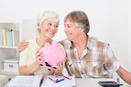 Portrait Of Smiling Senior Couple Saving Money In The Pink Piggybank photo