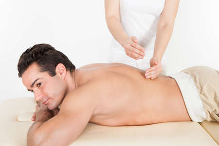 Shirtless Man Lying On Front Getting Spa Treatment photo