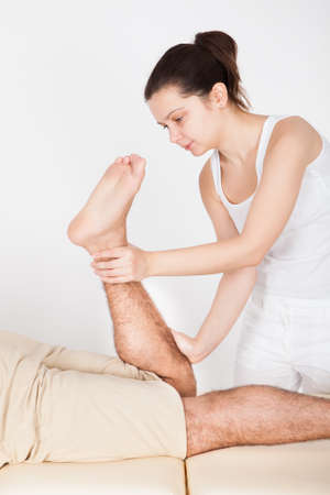 Young Man Lying On Table Getting Foot Massage From Masseuse Stock Photo - 25045927