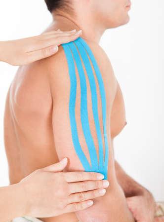 convulsion: Close-up De La Persona Solicitando Kinesio Tape Especial sobre el hombro del hombre Foto de archivo