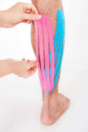 Close-up Of A Person Applying Kinesio Tape On Injured Calf photo