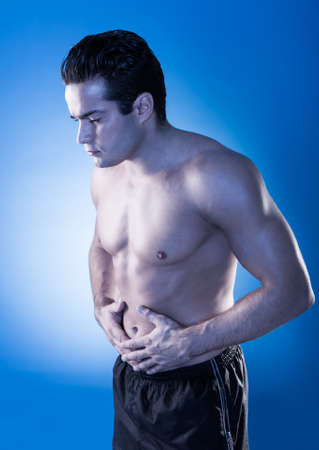 constipation symptom: Portrait Of Young Shirtless Man Having Stomachache