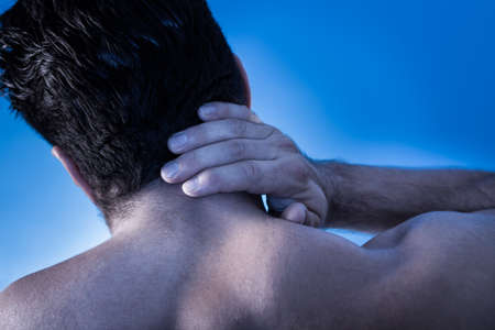 neck pain: Rear View Of Young Man Suffering From Neck Pain Stock Photo