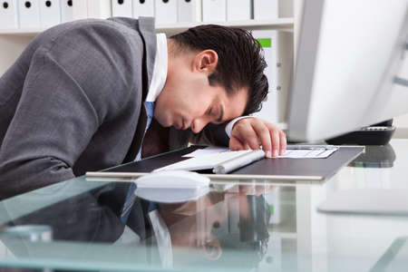 Portrait Of A Young Tired Businessman Sleeping At Desk photo