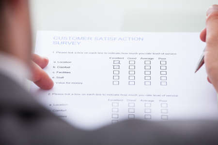 Close-up Of Businessman Filling Customer Survey Form Stock Photo - 25045938