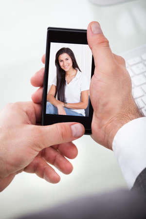 Close-up Of A Businessman Having A Videochat With Woman On Cellphone photo