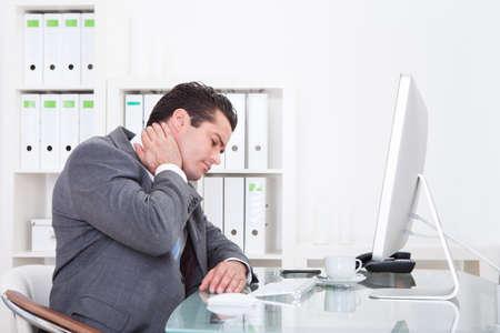 首の痛みに苦しんでいる机でオフィスで若いビジネスマン 写真素材