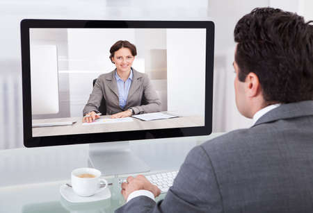 video conference: Close-up Of A Young Businessman Chatting With Her Colleague
