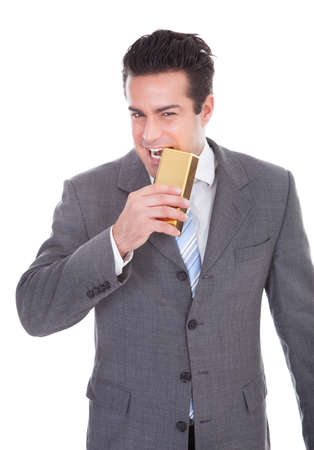 Portrait Of Young Businessman Biting Gold Bar Over White Background photo