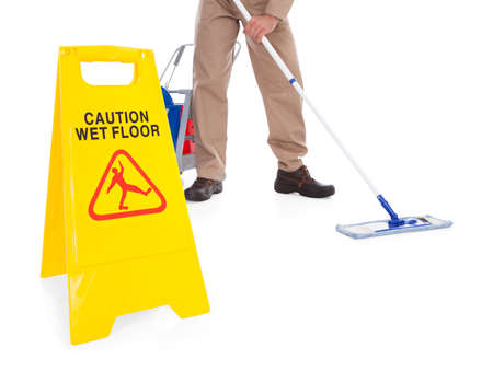 Close-up Of Male Sweeper Cleaning Floor On White Background With Warning Sign photo