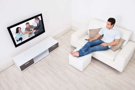 Young Man At Home Watching Movie On Television photo