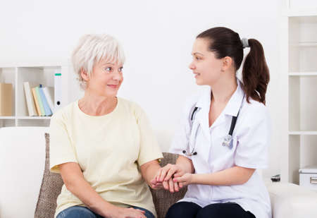 happy patient: Portrait Of Young Doctor Holding Hand Of Mature Patient