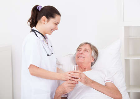 Young Female Doctor Giving Glass Of Water To Senior Patient photo