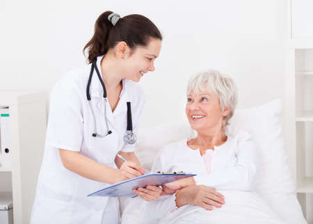 doctor writing: Senior Female Patient Looking At Doctor Writing On Clipboard