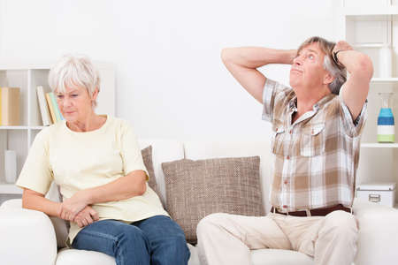 Portrait Of Senior Couple Sitting On Couch At Home Quarrelling With Each Other photo