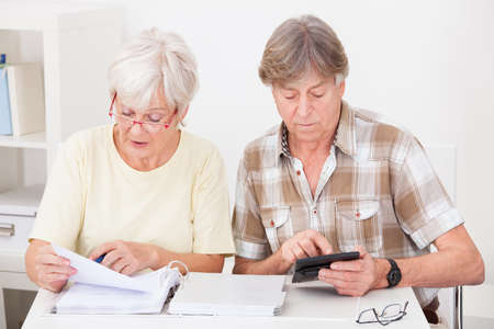adds: Elderly Woman Checking The Accounts While The Husband Adds Up The Figures On The Calculator