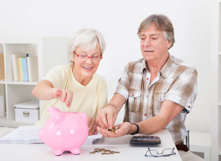 retirement couple: Portrait Of Smiling Senior Couple Calculating Coins In The Pink Piggybank