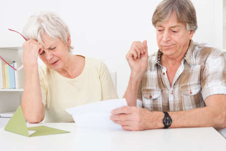 Senior Couple Were Disappointed While Reading Letter On Table photo