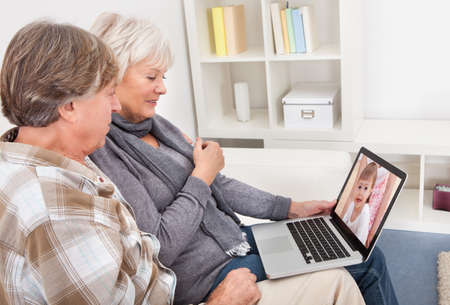 sofa television: Seniors Couple Looking At Laptop Screen With The Image Of Baby