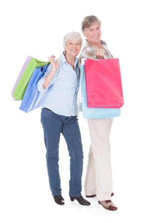 Portrait Of Happy Senior Couple Standing With Shopping Bag Over White Background photo