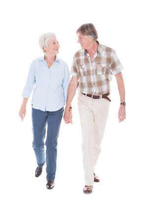 Happy Senior Couple Holding Hand And Walking Over White Background