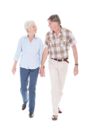 ancianos caminando: Pares mayores felices de la explotaci�n agr�cola de la mano y caminar Sobre Fondo Blanco