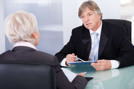 confident consultant: Mature Businessman Discussing With Businesswoman In Meeting Stock Photo
