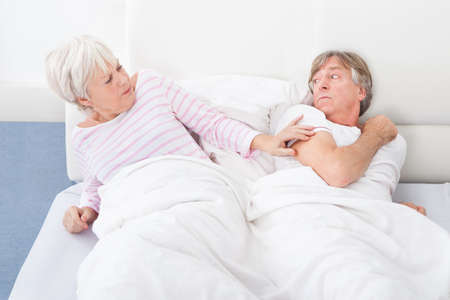Angry Senior Couple Lying On Bed Looking At Each Other photo