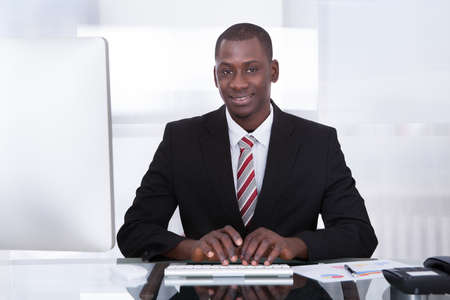 Happy Young African Businessman Using Computer At Desk Stock Photo - 25097007