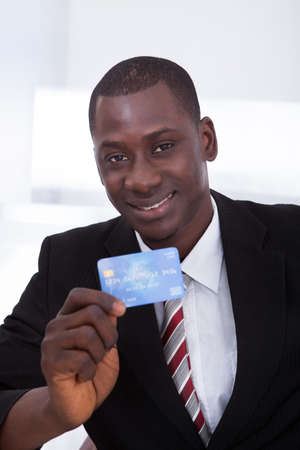 purchases: Portrait Of Happy African Businessman Holding Credit Card