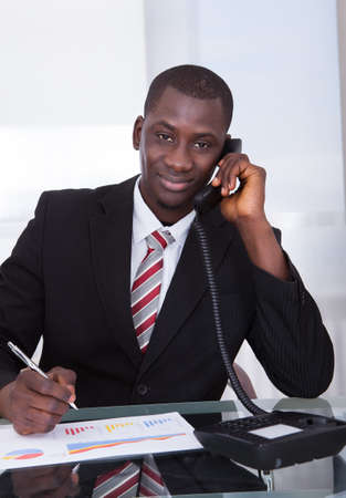 verbal: Young African Businessman Holding Pen Over Graph Talking On Telephone