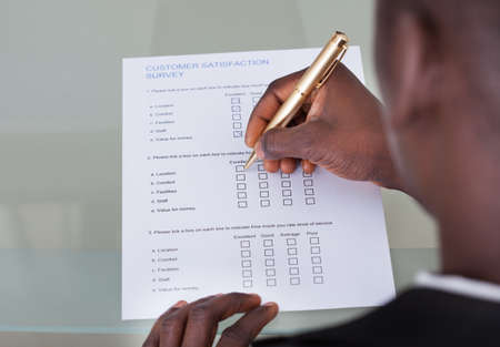Close-up Of Businessman Filling Customer Survey Form