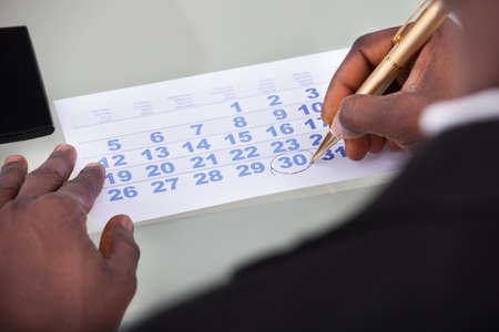 calendar date: Close-up Of Businessman Marking With Pen And Looking At Date On Calendar Stock Photo