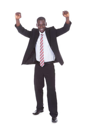 Portrait Of Excited Young Businessman With Hand Raised photo
