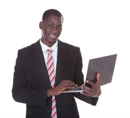 Young African Businessman Holding Laptop Over White Background photo
