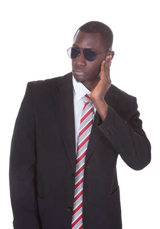 Portrait Of An African Young Man In Suit Wearing Sunglasses Over White Background photo
