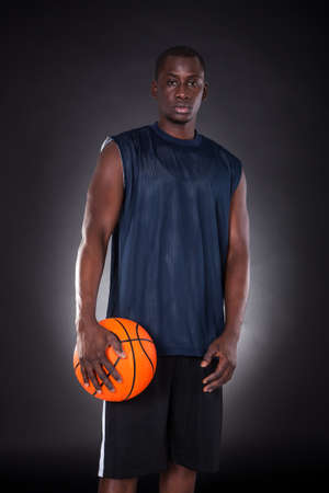 African Young Man With Basketball Over Black Background photo