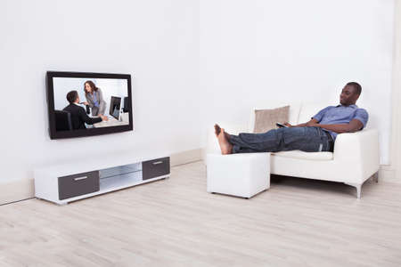 Young Man Resting In Sofa Watching Television Stock Photo
