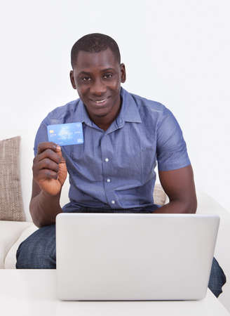 Happy African Man Holding Credit Card With Laptop On Table In Living Room photo