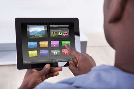 Close-up Of African Person Holding Digital Tablet Showing Icons photo