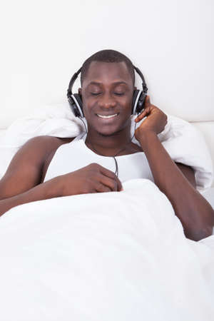 African Man Listening To Music Through Headphones photo