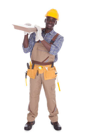 Young Happy Craftsman Carrying Floor Tiles Over White Background photo