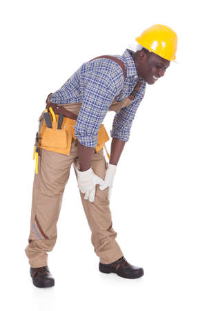 Young Male Repairman Suffering From Knee Pain Over White Background photo