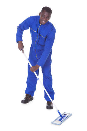 Young Man In Blue Suit Cleaning The Floor Over White Background photo