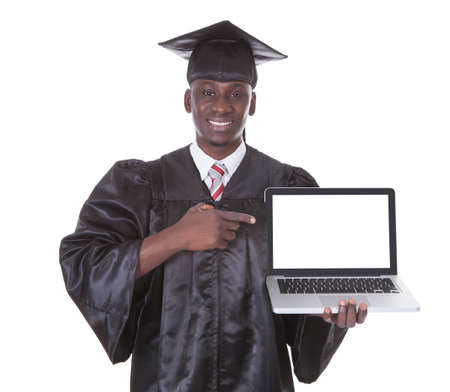 academic achievement: Male Student In Graduate Robe Pointing Towards Laptop Over White Background