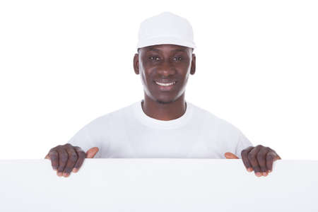 Portrait Of Male Painter Holding Blank White Banner Over White Background photo