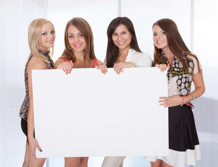 Four Happy Young Women Holding Blank Placard Stock Photo - 25149138