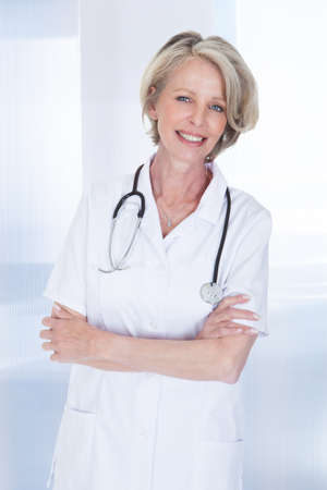 Portrait Of Happy Mature Female Doctor With Stethoscope photo
