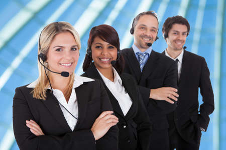 Confident business team with headset standing in a line against white  photo